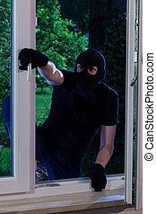 Masked man entering the house