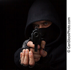 Masked robber with gun aiming into the camera against a ...