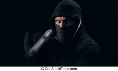Dangerous masked thief aiming with gun over black background. Man in black sweater with hood standing in studio with weapon.