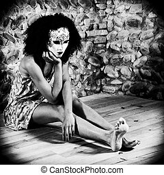 Masked woman sitting on the floor.
