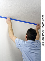 Masking a Wall with Blue Tape - Adult male pressing blue...
