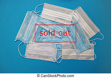 Masks on a blue background and a sign showing SOLD OUT in red text. Coronavirus panic, purchase shortage of medical face masks, problems with stocks of medical equipment.