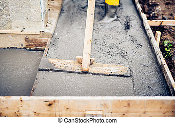 Mason building and leveling a first layer of fresh concrete floor at house stairs and sidewalks, construction site