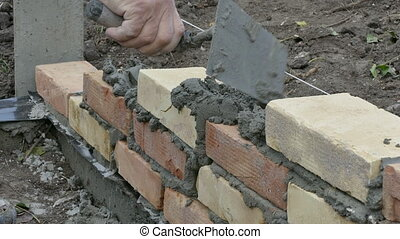 Mason building brick wall - Mason making wall with mortar...