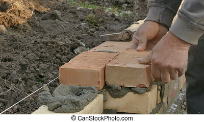 Mason building brick wall - Mason making wall with mortar...
