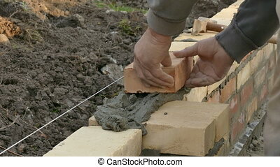 Mason building wall with mortar and bricks - Mason making...