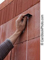 Mason checking wall is straight