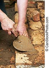 Mason hands at bricklaying works