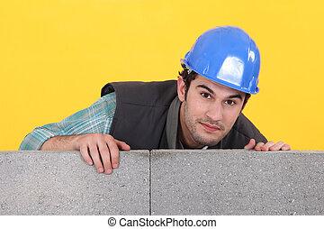 Mason making sure wall is level