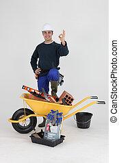 Mason making the OK gesture by wheelbarrow