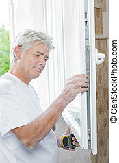 Mason measuring up a window
