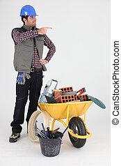Mason stood by wheelbarrow pointing