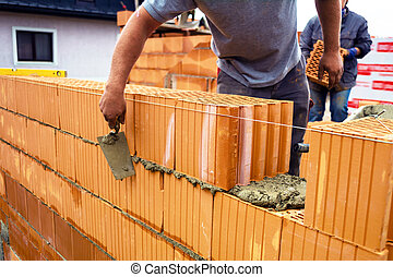 mason with brick on construction site