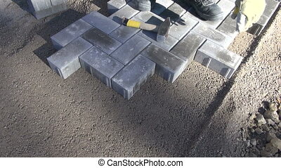 mason worker making new sidewalk pavement with stone bricks