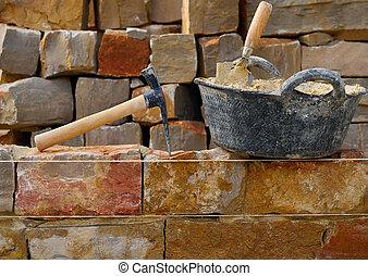 Masonry stone wall construction with tools