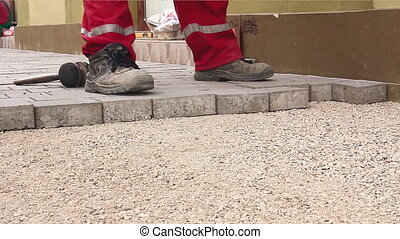Masons are fitting flagstone, low angle view until they making footpath in city street. Masons hands are fitting flagstone