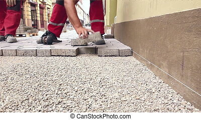 Masons are fitting flagstone, low angle view until they making footpath in city street.