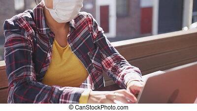 masque, coronavirus, femme, mélangé, porter, course, ordinateur portable, fonctionnement