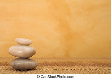 hot stone massaging stones on bamboo cloth in front of wall - copy space