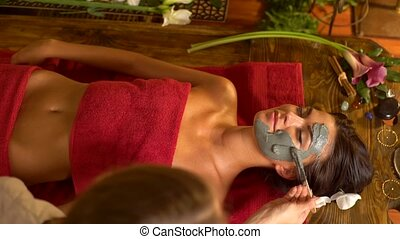 Massage and clay body mask in spa salon.Top view. 4k. -...