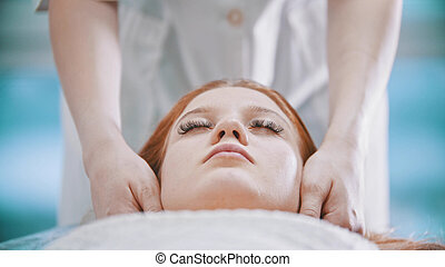 Massage - female masseuse kneading the chin area to a young woman using her palms