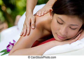 Massage hands - A young woman enjoying a massage outside