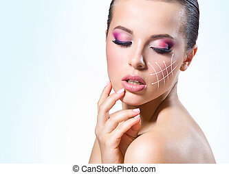 Massage lines on the girl face, on blue background. Concept...