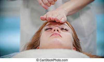 Massage - masseuse is kneading her clients face with palms