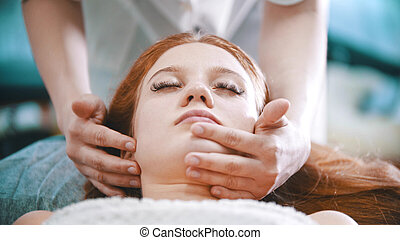Massage - masseuse kneading the chin area to a young woman using her palms