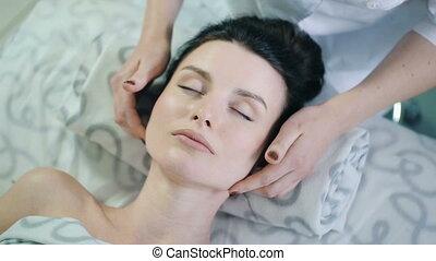 massage of a woman's face - massage therapist massaging...