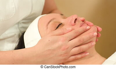Dolly close-up shot of massage therapist doing a facial massage at beauty treatment salon