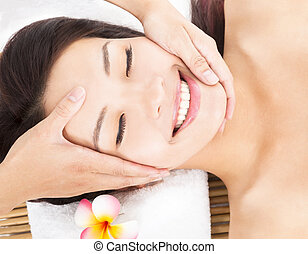 massage of face for asian woman in spa salon