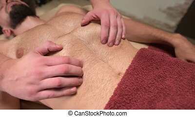 massage of the diaphragm and placement of organs in the abdominal cavity of a male athlete by a physiotherapist. Alternative medicine.