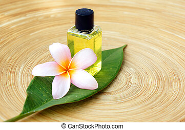 Massage oil for tropical spa concept with plumeria flowers on wooden plate