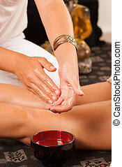 Massage therapist moistening her hands in oil