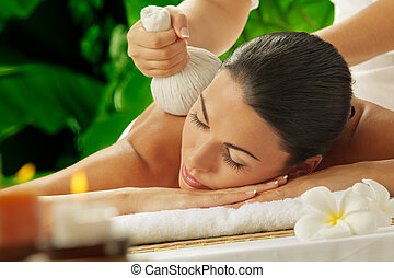 massage on green - portrait of young beautiful woman in spa...