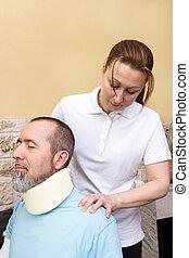 Massage - A therapist massages the neck of an injured man