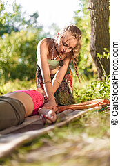 Massage professional impliments her massage abilities outside.