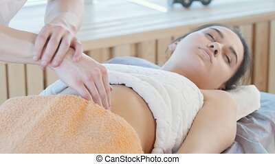 Massage session. A masseur giving a relaxing stomach...