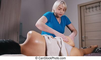 Massage session. A woman laying on the couch on her side and...