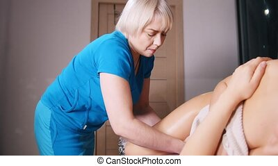 Massage session. A woman laying on the side and receiving a...
