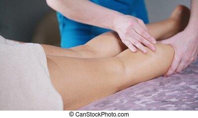 Massage session. A woman receiving a legs massage. Mid shot