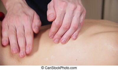 Massage session. Young woman receiving a massage. Masseur taping womans oiled back