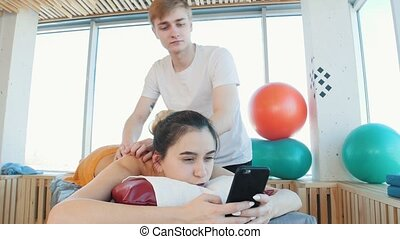 Massage session. Young woman sitting in her phone while...