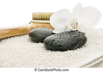 Massage stones, brush and orchid on a towel