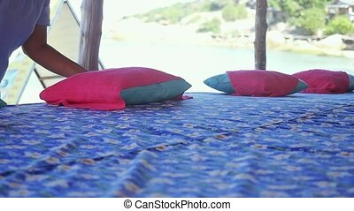 Massage table on the beach with the hands of the masseuse corrects the pillow in slow motion.