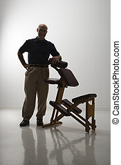 Massage therapist and chair. - Silhouette of Caucasian...
