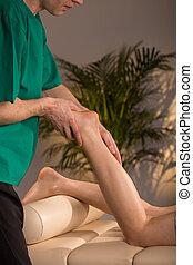 Massage therapist doing functional massage - Male adult...
