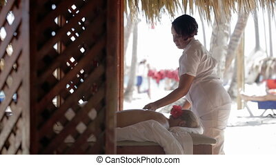 Female massage therapist finishing spa treatment and covering the womans back with sheet. Tropical beauty spa