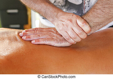 Massage therapist in action - Massage therapist working with...
